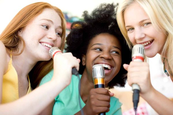 B6E1K3 Karaoke. Teenage girls singing into microphones.