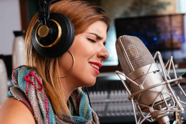 Close-up portrait of beautiful woman in headphones singing